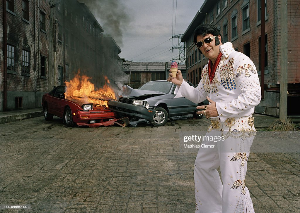Celebrity impersonator with ice cream cone in front of car crash : Stock Photo