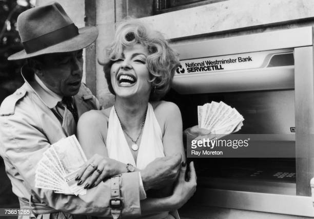 Celebrity lookalikes Vicki Scott and Kenny Whymark withdraw 100 pounds each to inaugurate National Westminster Bank's 500th cashpoint machine...