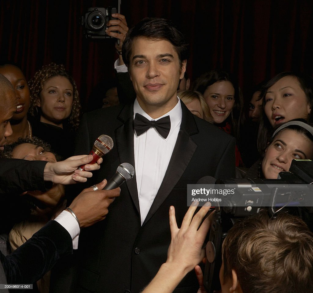 Celebrity male in tuxedo talking to fans and media at event, portrait : Stock Photo