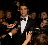 Celebrity male in tuxedo talking to fans and media at event, portrait