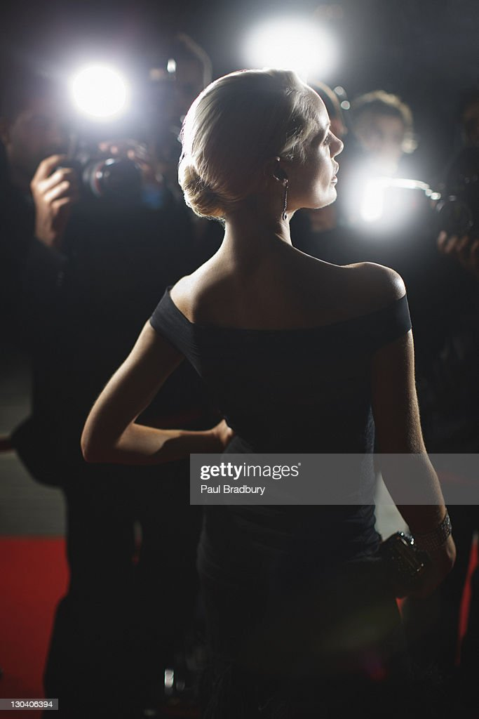 Celebrity posing for paparazzi on red carpet : Stock Photo
