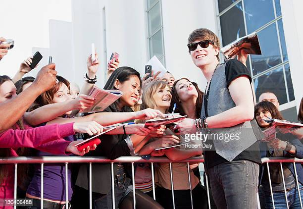 Celebrity signing autographs for fans