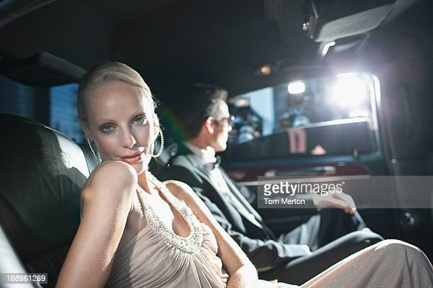 Celebrity sitting in backseat of car