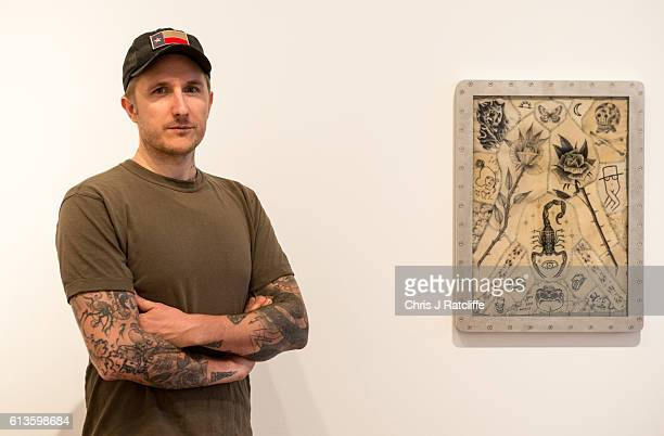 Celebrity tattoo artist Scott Campbell poses for a photograph next to some of his artwork at his event 'Whole Glory' on October 9 2016 in London...
