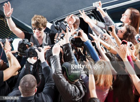 Celebrity waving to paparazzi and fans