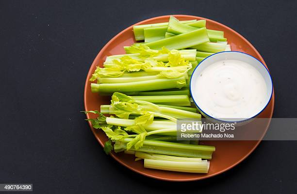 Celery sticks with leaves on few of them and a bowl full of delicious ranch sauce placed in a brown plate against a black background