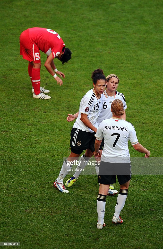 Celia Okoyino da Mababi of Germany celebrates with team mates Martina Mueller and <a gi-track='captionPersonalityLinkClicked' href=/galleries/search?phrase=Melanie+Behringer&family=editorial&specificpeople=766499 ng-click='$event.stopPropagation()'>Melanie Behringer</a> after scoring a goal during the UEFA Womens Euro 2013 qualification match between Germany and Turkey at Schauinsland-Reisen-Arena on September 19, 2012 in Duisburg, Germany.
