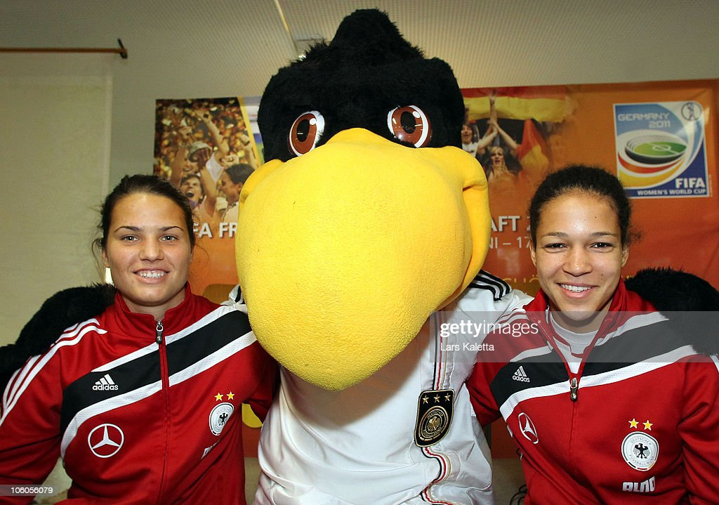 Celia Okoyino da Mbabi (R) and Dzsenifer Marozsan (L) pose with the Mascot during a visit of the Women National Team of Germany at the Hans-Andersen-School on October 26, 2010 in Wolfsburg, Germany.