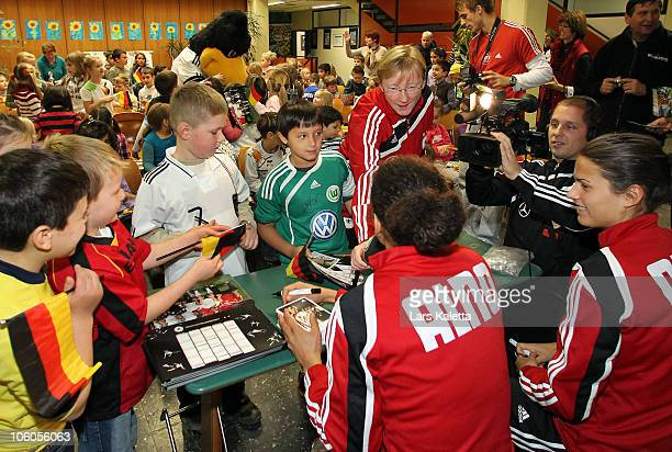 Celia Okoyino da Mbabi and Dzsenifer Marozsan sign autographs during a visit of the Women National Team of Germany at the HansAndersenSchool on...