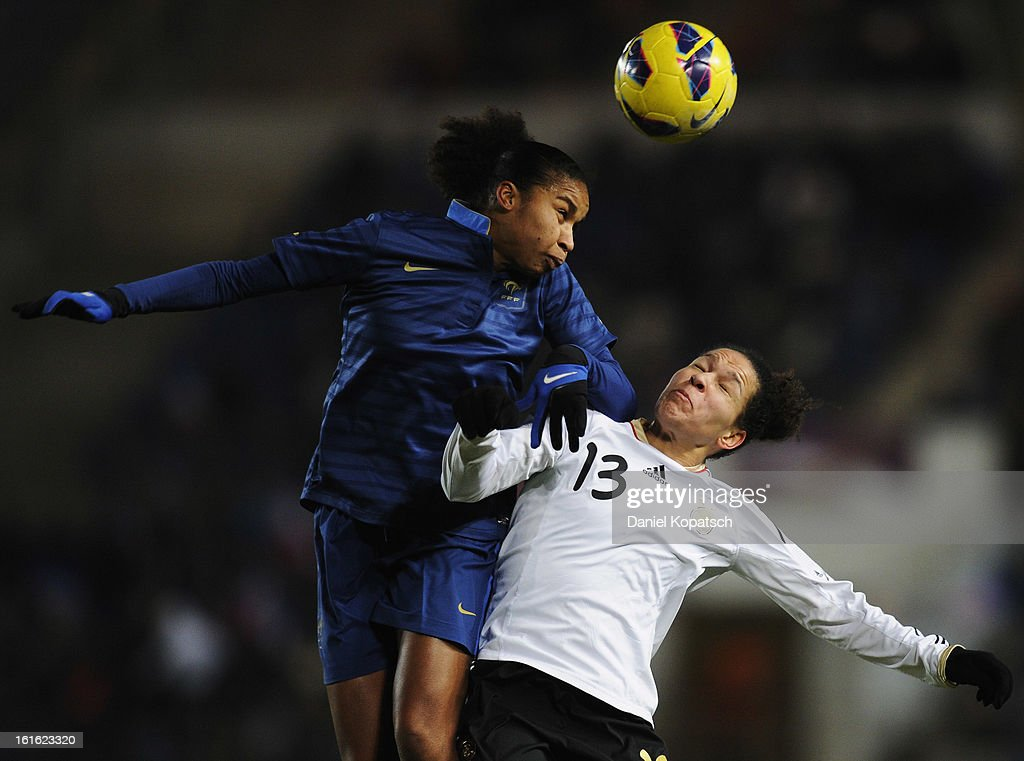 Celia Okoyino da Mbabi of Germany (R) jumps for a header with Laura Georges of France during the international friendly match between France and Germany at Stade de la Meinau on February 13, 2013 in Strasbourg, France.