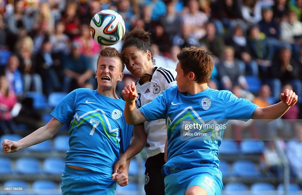 Celia Sasic (C) of Germany jumps for a header with Andreja Nikl (L) and Lucija Grad of Slovenia during the FIFA Women's World Cup 2015 qualifying match between Germany and Slovenia at Carl-Benz-Stadion on April 10, 2014 in Mannheim, Germany.