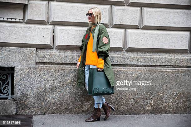 Celine Aagaard wears Celine sunglasses a long green Whyred armystyle coat with patches an orange knit sweater FW16 green Gucci XL leather tote cuffed...
