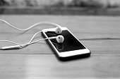 Cell phone and ear phone on wooden table in black and white
