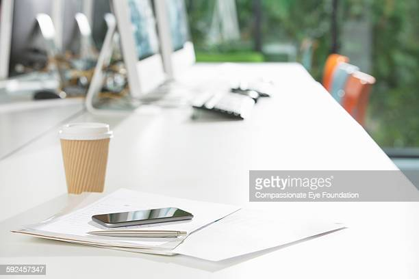 Cell phone and paperwork on desk in office