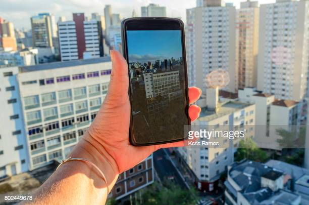 Cell phone in hand with building background