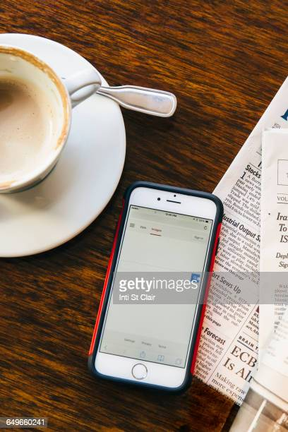 Cell phone, newspaper and coffee cup in cafe