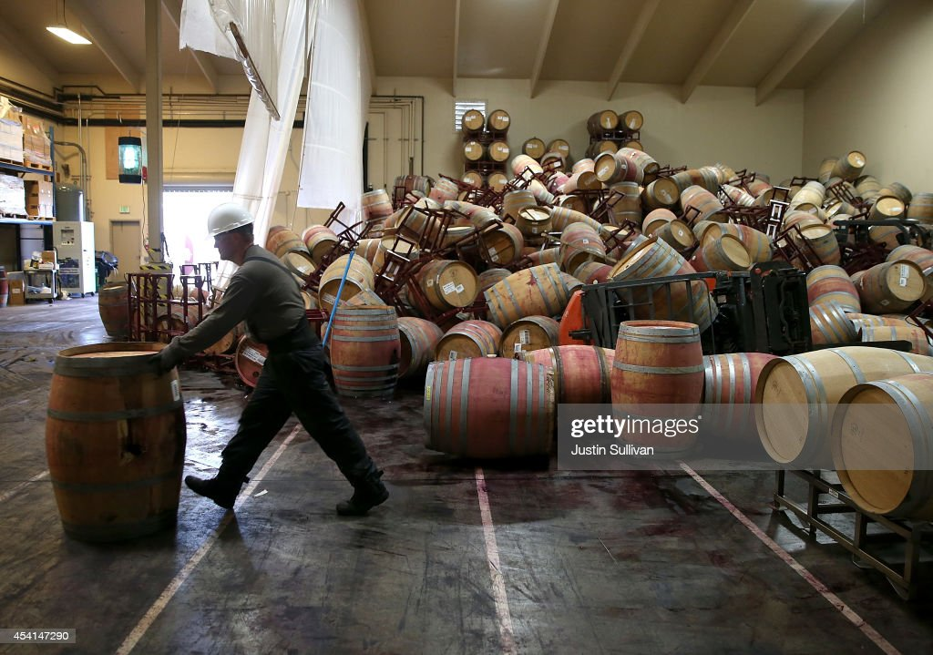 Cellar worker Adam Craig moves a wine barrel as he cleans up a pile of collapsed barrels in a storage room at Kieu Hoang Winery on August 25, 2014 in Napa, California. A day after a 6.0 earthquake rocked the Napa Valley, residents and wineries are continuing clean up operations.