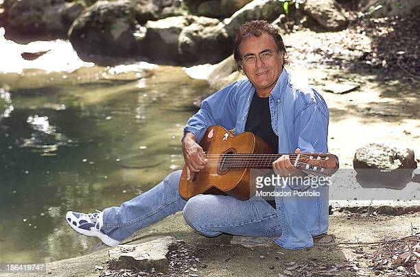 the italian singer Albano Carrisi in art Al Bano posing with his guitar near a pond in his estate in Puglia Cellino San Marco 2002