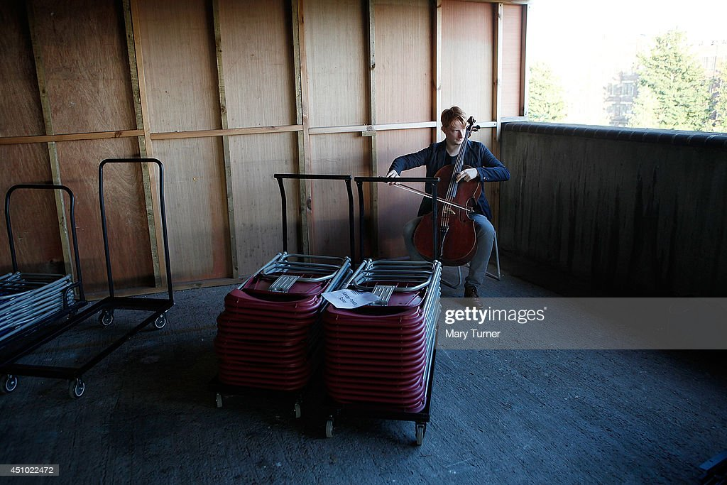 A cellist from the Multi-Story Orchestra practices behind stacked up chairs, before a performance of Jean Sibelius' 5th Symphony at the Peckham Rye Car Park on June 21, 2014 in London, England. The performance is one of a series that the orchestra will be performing in the South London car park throughout the summer, hoping to bring classical music to new audiences.