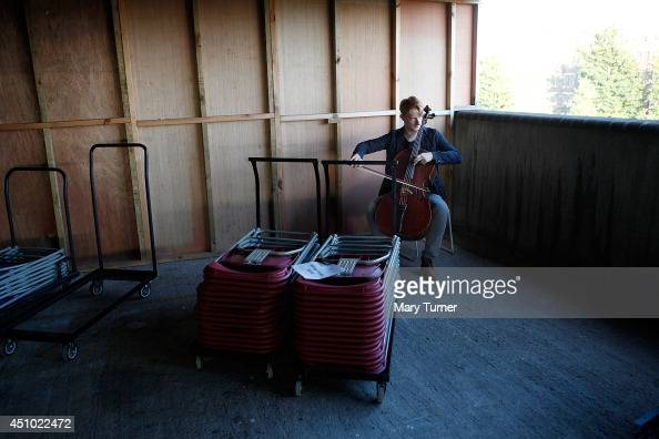 A cellist from the MultiStory Orchestra practices behind stacked up chairs before a performance of Jean Sibelius' 5th Symphony at the Peckham Rye Car...