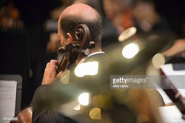 Cellist in symphony orchestra during performance (selective focus)