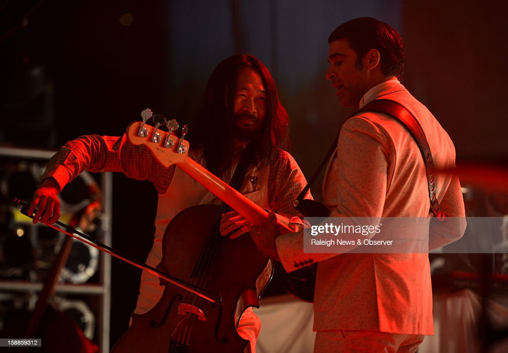 Cellist Joe Kwon, left, and bassist Bob Crawford of the Avett Brothers perform Monday, December 31, 2012, in Greensboro, North Carolina.