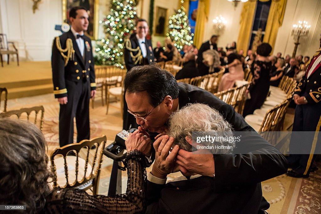 Cellist Yo-Yo Ma hugs Itzhak Perlman while kissing the hand of Perlman's wife Toby at the Kennedy Center Honors reception at the White House on December 2, 2012 in Washington, DC. The Kennedy Center Honors recognized seven individuals - Buddy Guy, Dustin Hoffman, David Letterman, Natalia Makarova, John Paul Jones, Jimmy Page, and Robert Plant - for their lifetime contributions to American culture through the performing arts.