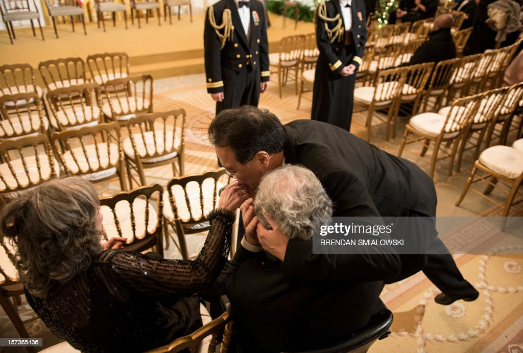 Cellist Yo-Yo Ma (R) kisses violinist Itzhak Perlman's (C) wife's, Toby Perlman, hand while greeting the couple before an event in the East Room of the White House December 2, 2012 in Washington, DC. US President Barack Obama and First Lady Michelle Obama attended the event at the White House with the 2012 Kennedy Center Honorees to celebrate their contribution to the arts before heading to the Kennedy Center for the honors program. AFP PHOTO/Brendan SMIALOWSKI
