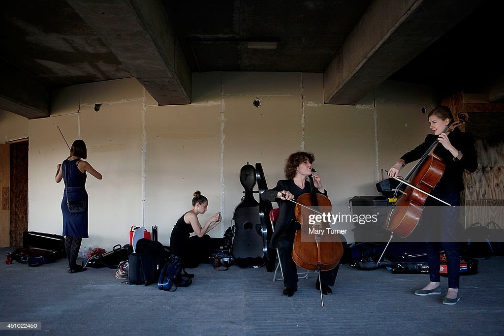 Cellists from the Multi-Story Orchestra practices before a performance of Jean Sibelius' 5th Symphony at the Peckham Rye Car Park on June 21, 2014 in London, England. The performance is one of a series that the orchestra will be performing in the South London car park throughout the summer, hoping to bring classical music to new audiences.