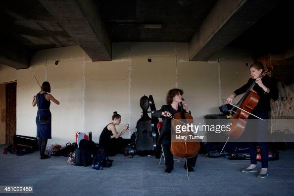 Cellists from the MultiStory Orchestra practices before a performance of Jean Sibelius' 5th Symphony at the Peckham Rye Car Park on June 21 2014 in...