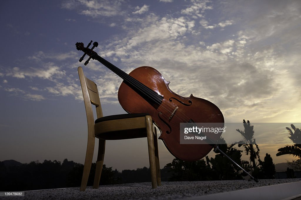 Cello leaning against a chair at sunset. : Stock Photo
