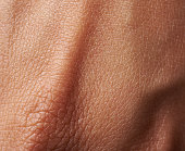 Cells on woman dark skin close up. Macro of human skin texture