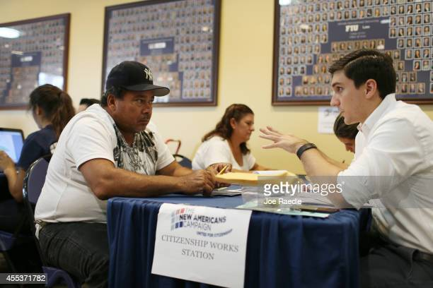 Celso Solano originally from Nicaragua speaks with Camilo Rodriguez a Florida International University law student as he is given assistance in...