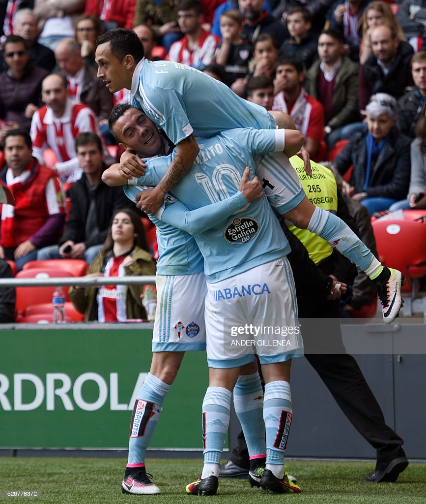 Celta Vigo's Chilean forward Fabian Orellana (up) is congratulated by teammates forward Iago Aspas (L) and forward Nolito (C) after scoring during the Spanish league football match Athletic Club de Bilbao vs RC Celta de Vigo at the San Mames stadium in Bilbao on May 1, 2016. / AFP / ANDER