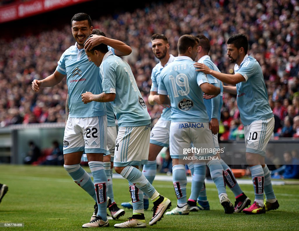 Celta Vigo's Chilean forward Fabian Orellana (2ndL) is congratulated by Argentinian defender Gustavo Cabral (L) after scoring during the Spanish league football match Athletic Club de Bilbao vs RC Celta de Vigo at the San Mames stadium in Bilbao on May 1, 2016. / AFP / ANDER
