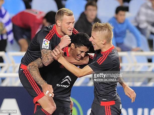 Celta Vigo's Chilean midfielder Pablo Hernandez celebrates a goal with teammates Swedish forward John Guidetti and Danish defender Daniel Wass during...