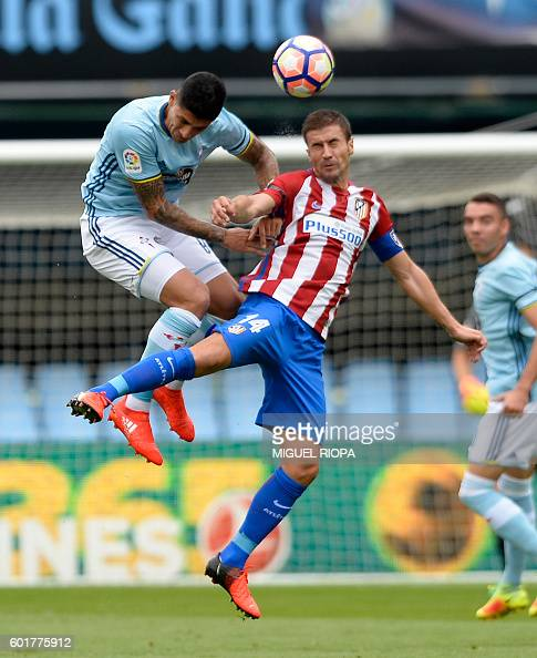 Celta Vigo's Chilean midfielder Pablo Hernandez jumps for the ball with Atletico Madrid's midfielder Gabi during the Spanish league football match RC...