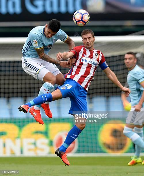 Celta Vigo's Chilean midfielder Pablo Hernandez jumps for the ball with Atletico Madrid's midfielder Gabi during the Spanish league football match RC...