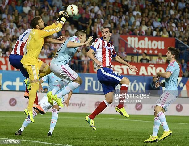 Celta Vigo's goalkeeper Sergio Alvarez clears the ball past Atletico Madrid's Uruguayan defender Diego Godin during the Spanish league football match...