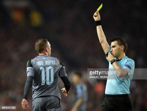 Celta Vigo's Spanish striker Iago Aspas is booked by Romanian referee Ovidiu Hategan for simulation during the UEFA Europa League semifinal secondleg...