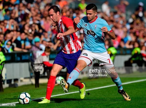 Celta Vigo's Uruguayan forward Maxi Gomez vies with Atletico Madrid's Uruguayan defender Diego Godin during the Spanish league football match RC...