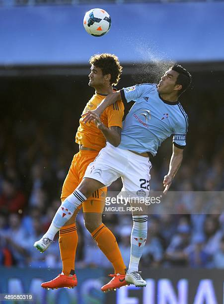 Celta's Argentinian midfielder Augusto Fernandez heads the ball as he vies with Real Madrid's Willian Jose during the Spanish league football match...
