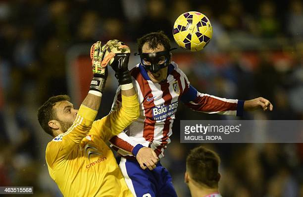 Celta's goalkeeper Sergio Alvarez jumps for the ball with Atletico Madrid's Uruguayan defender Diego Godin during the Spanish league football match...
