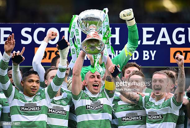 Celtic captain Scott Brown is presented with the League Cup trophy by life long Celtic fan Rod Stewart as the Celtic team celebrate during the...