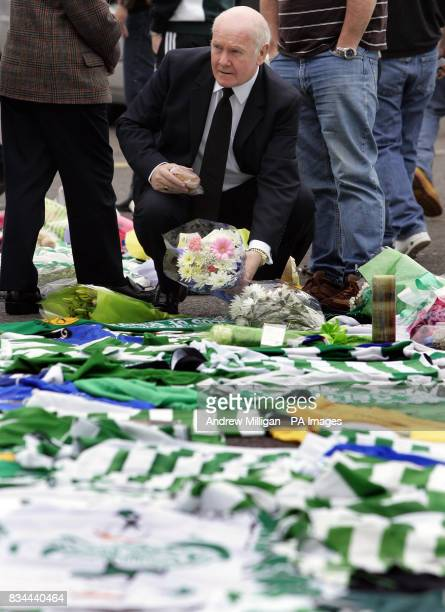 Celtic Chairman John Reid looks at flowers after tributes are left for Tommy Burns at Celtic Park Glasgow