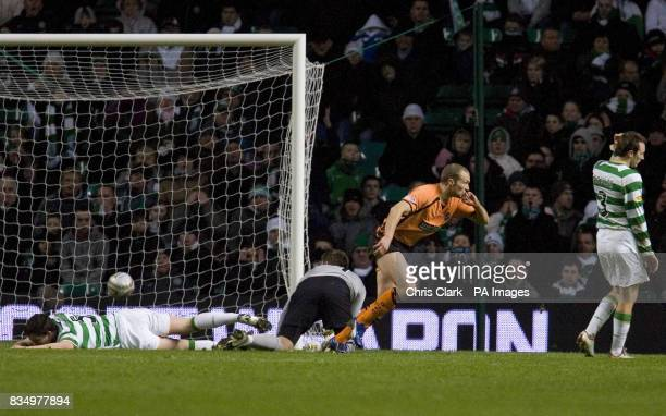 Celtic defender Gary Caldwell and goalkeeper Artur Boruc lie dejected on the ground as Dundee United's Warren Feeney wheels away in celebration after...