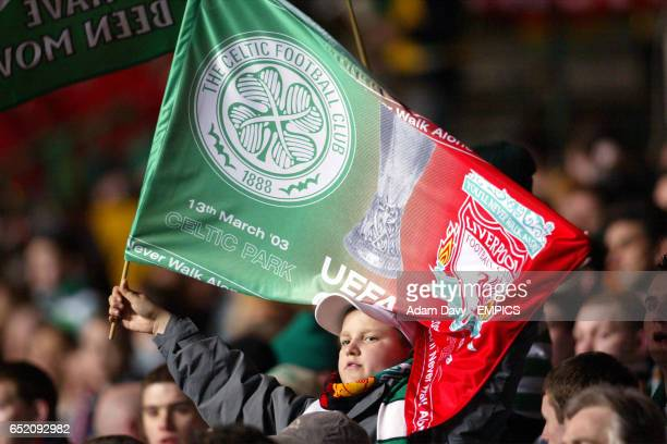 A Celtic fan gets into the spirit of things prior to kick off with a split Celtic and Liverpool flag