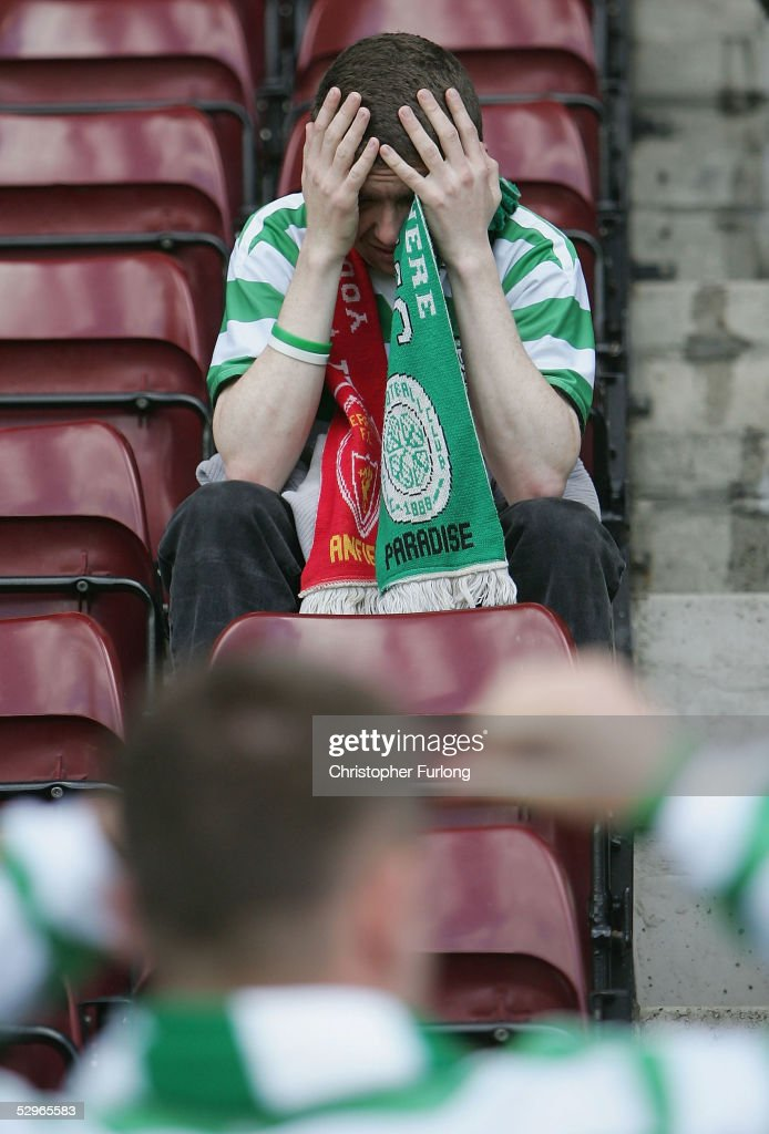A Celtic fan holds his head in his hands after Celtic lost 2-1 to Motherwell resulting in their rivals Glasgow Rangers lifting the league title after the Scottish Premier League match between Motherwell and Celtic at Fir Park on May 22, 2005, Motherwell, Scotland.