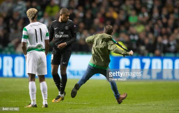 Celtic fan ran on the pitch and aimed a kick at Kylian Mbappe of Paris Saint Germain during the UEFA Champions League Match between Celtic and Paris...