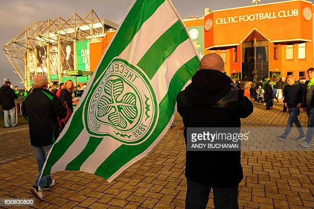 A Celtic fan with a flag stands outside Celtic Park in Glasgow on December 17 2016 before the Scottish Premiership football match between Celtic and...